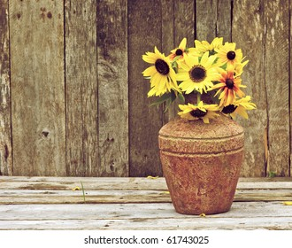 Sunflowers  in a vase on a rustic, grunge background with copy space.