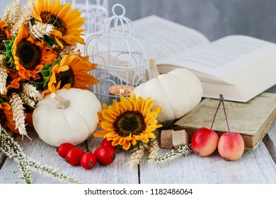 Sunflowers, white pumpkins and open book. Beautiful autumn table decoration.