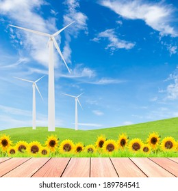 sunflowers with wind turbine on green grass field against blue sky background and wood plank foreground,used for green earth concept