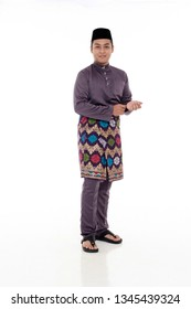 SUNGAI PETANI,MALAYSIA - MARCH 21TH 2019:portrait young and handsome man with hands holding watch standing on white background.Hari Raya Aidilfitri celebration concept.