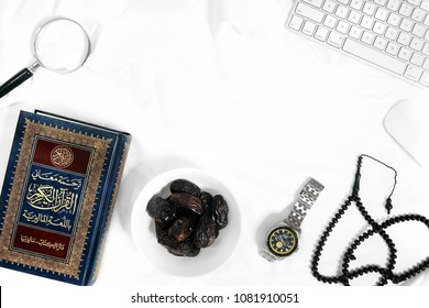 SUNGAI PETANI,MALAYSIA - MAY 2TH 2018 : conceptual iftar in bed with Quran ,dates ,watch, rosary, keyboard, mouse and magnifying glass.copy space.flatlay