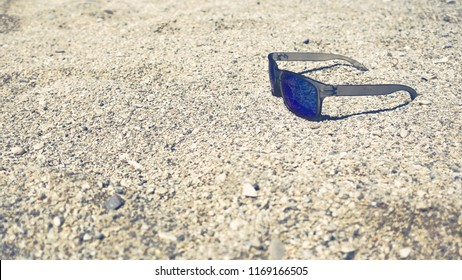 Sunglases on sandy beach during a sunny day.