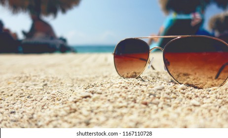 Sunglases on sandy beach with the sea and blue sky.
