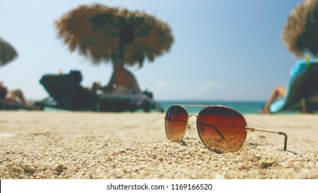 Sunglases on sandy beach with sun shades during a sunny day.