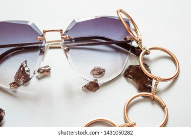 Sunglases. Summer eyeglases. Fashionable background with rings, jewelry stones, sunglases.