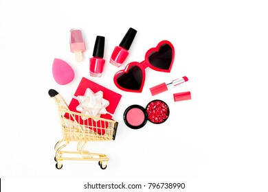 Sunglass, gift and cosmetics in a shopping cart on a white background. Valentines day shopping. Flat lay, top view