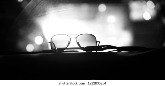Sunglass kept on a dashboard of a car unique black and white photo