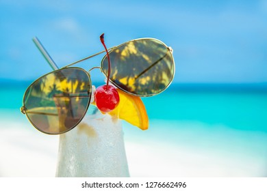 sunglass on cocunut cocktail and sea background on clear sky day