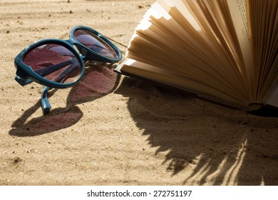 Sunglasses and book on sand selective focus horizontal filtered