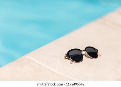 sunglasses by the pool on a sunny summer day. summer background.