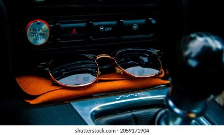 Sunglasses in a car with start button and shifter