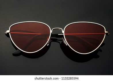 sunglasses cat's eye with red glasses in metal frame isolated on black