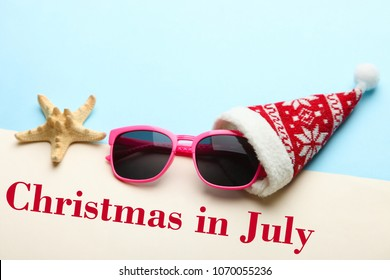 Sunglasses in a Christmas cap on a beige and blue background. The concept of summer Christmas.