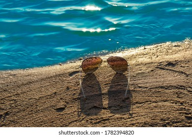 Sunglasses with colored glass on sand, beach and travel concept