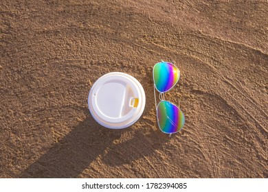 Sunglasses with colored glasses and disposable cup on sand, sea beach and travel concept