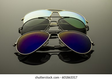 Sunglasses different in shape and color pairs on a dark background with reflection