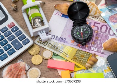 Sunglasses, euro money, compass and notepad lying on wooden background.