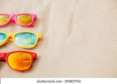 sunglasses for Family. Red, pink, yellow sunglasses on the sand background. on the beach with reflection of sky and trees