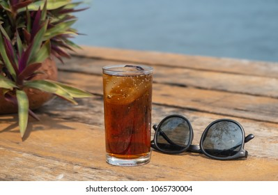Sunglasses and a glass of cola or coke with ice cubes on a wooden bridge