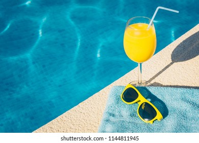 Sunglasses and a glass of orange juice in the resort hotel