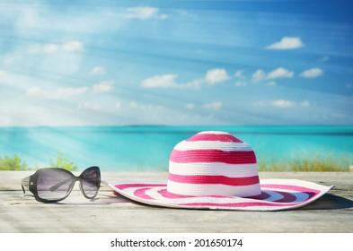 Sunglasses and hat against ocean
