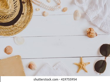 Sunglasses, hat and  book on a wooden background. Top view
