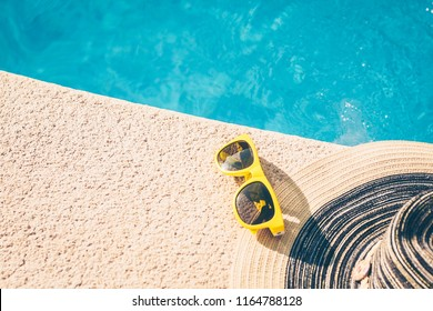 Sunglasses and hat on the poolside - girl on vacation