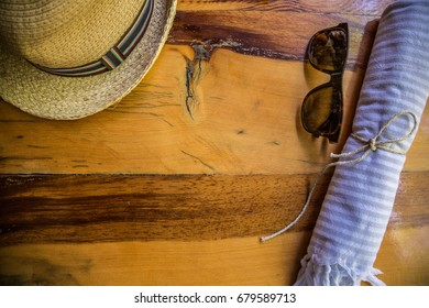 Sunglasses, hat and towel on the wooden table