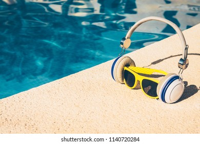 sunglasses in headphones listen to music near the pool, a fun picture of a tropical vacation