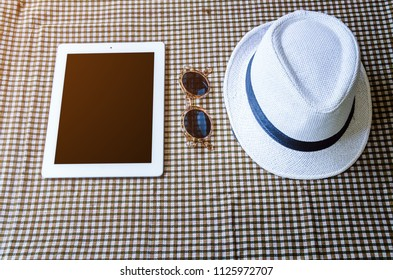 sunglasses with laptop computer and white hat, summer traver concept.