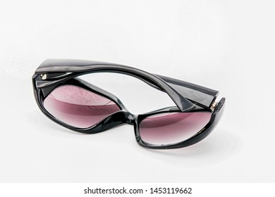 sunglasses lying on glasses on white background