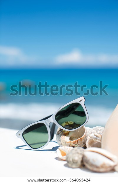 sunglasses lying on tropical sand beach. party. white towel on desk and red glasses with seashells. Sunglasses on the beach. Beautiful sea view wallpaper, background