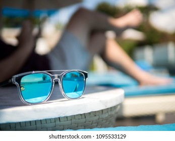 Sunglasses, Men's legs resting in a swimming pool background. Summer holiday traveling concept design banner with copyspace.