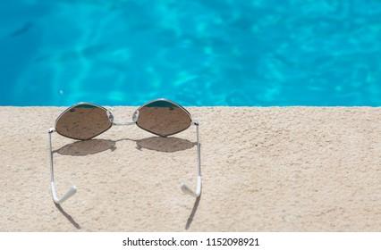 Sunglasses near the edge of a swimming pool