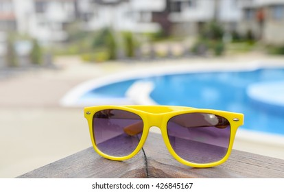 Sunglasses on a background of the pool. Close-up.