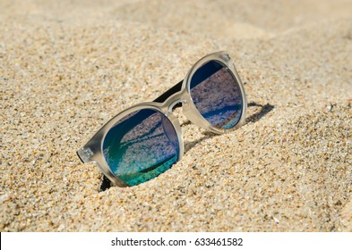 Sunglasses on the beach. Multi colored stylish model with transparent frame and blue-green lenses. Vacation concept.