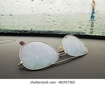 Sunglasses on console car with background is the sea in front of car in the rainy day.