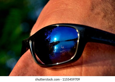 Sunglasses on the face in which the sunset reflects.