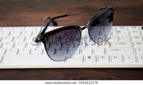 sunglasses on the keyboard on the wooden table