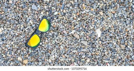 Sunglasses on a pebble beach