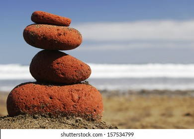 Sunglasses on red stone stack on the beach