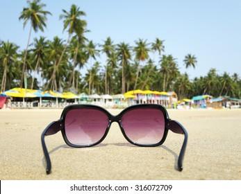 Sunglasses on the sand of Palolem beach. South Goa, India