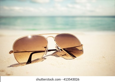 Sunglasses on sandy beach in summer - vintage color styles