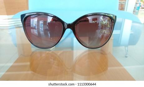 Sunglasses on transparent glass table minimalism