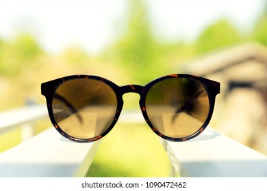 Sunglasses on white wooden bench, backyard in the background. Summer and fashion