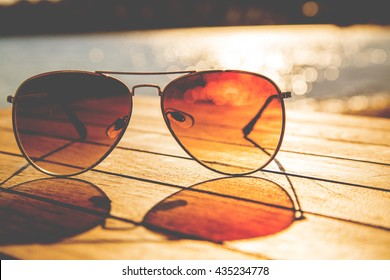 Sunglasses on a wooden table and rays of sunlight
