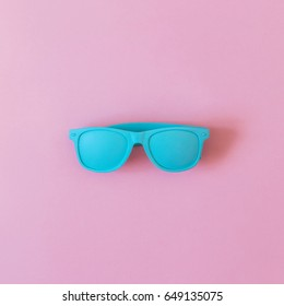 sunglasses painted in blue on a pink background. ultra minimal. flat lay. fashion summer.