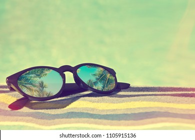 Sunglasses with palm trees reflections on a bath towel, vintage summer concept