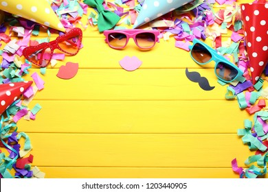 Sunglasses with paper caps and confetti on yellow wooden table