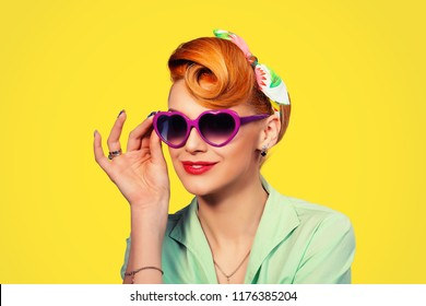 Sunglasses. Portrait of cute young pinup girl woman with retro 50s vintage hair style holding showing pink heart shaped sunglasses looking away happy in green buttoned shirt isolated on yellow wall.